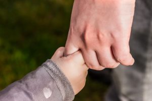 small child holding dad's hand